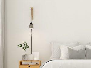 Arandela minimalista do lado de uma cama de casal