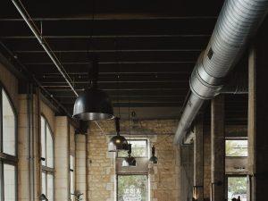 Restaurante com decoração industrial no teto, com luminárias e tubulações evidentes