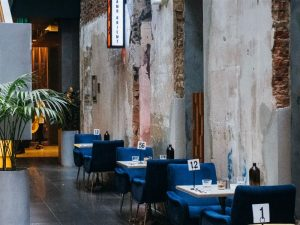 Várias mesas enfileiradas em um restaurante de paredes quebradas e luminárias industriais