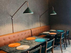 Mesas de lanchonetes sendo iluminadas por arandelas