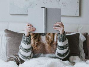 Mulher deitada na cama com um livro aberto na frente do rosto