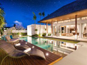 Jardim com piscina e deck ao lado durante a noite todo iluminado