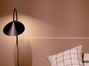 Luminária em cima da mesa de cabeceira do lado da cama de casal formando um cantinho de leitura