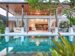 Piscina no jardim iluminada com a cozinha da casa ao fundo toda iluminada e lustre no teto