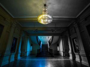 Lustre clássico no teto e ao fundo duas escadas opostas