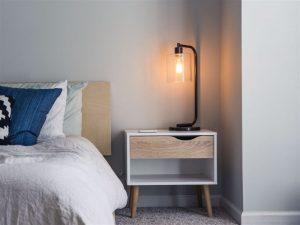 Luminária no canto do quarto em cima de uma mesa de cabeceira