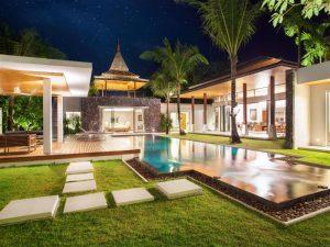 Ampla área de jardim com árvores e piscina iluminados