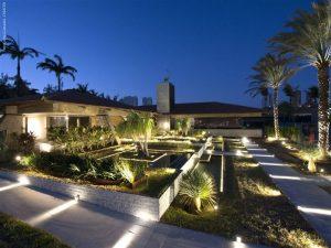 Jardim amplo com iluminação nos rodapés no chão durante a noite
