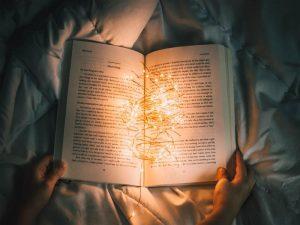 Pessoa deitada na cama com livro no colo cheio de luzes pequenas de cores quentes dentro dele visto de cima