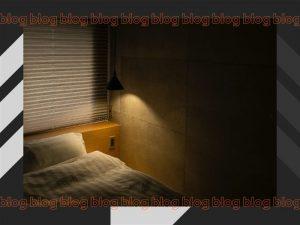 Quarto de caso com lâmpada suspensa na lateral do colchão