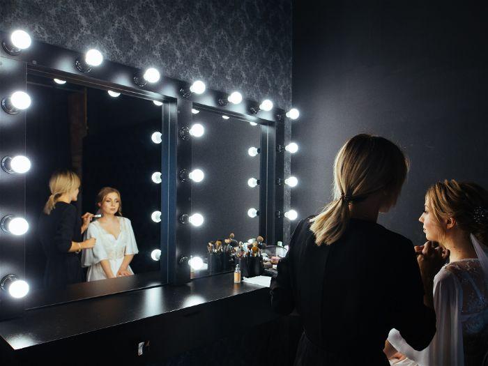 Mulher sendo maquiada em frente a um espelho profissional