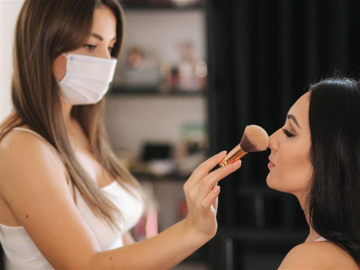 Mulher sendo maquiada em um estúdio com iluminação profissional