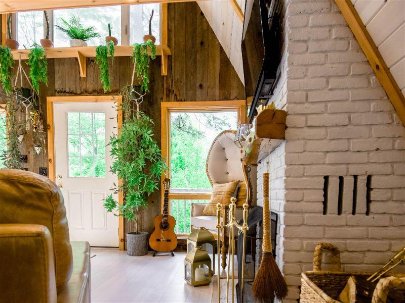 Ambiente de entrada de uma casa com estilo boho, paredes de madeira e tijolo, bem como diversos objetos e plantas disposto no ambiente