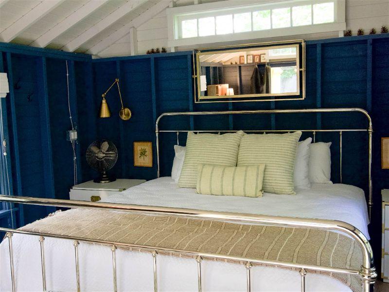 Quarto com paredes de madeira pintadas de azul escuro e cama de ferro com tecido e travesseiros com cores claras e listradas