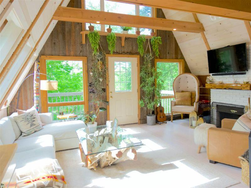 Sala com decoração estilo boho, estrutura da casa em madeira, móveis claros e alguns tecidos coloridos e algumas plantas penduradas na parede próximo porta