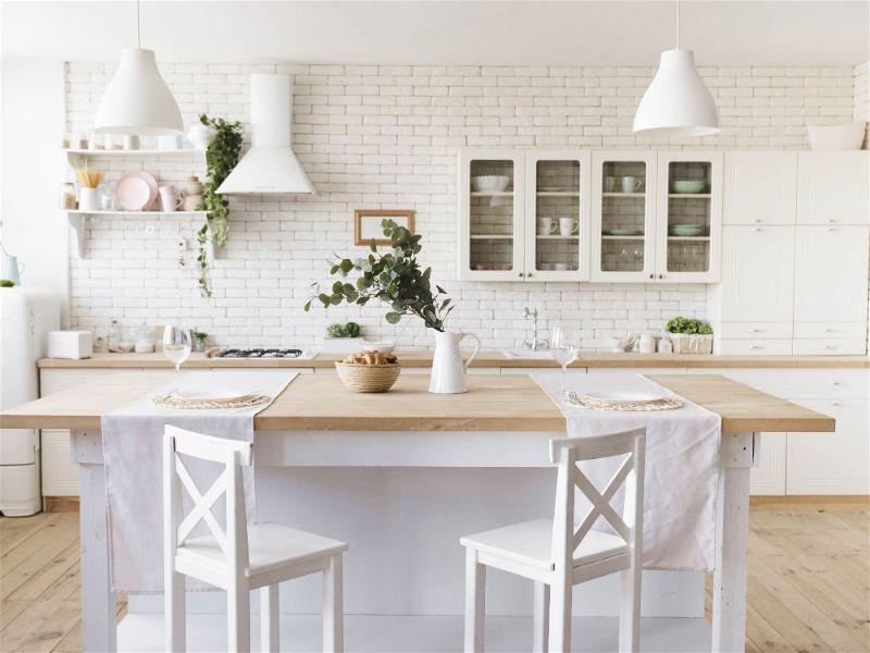 Cozinha grande com mesa central, móveis e decoração clara, bem como iluminada