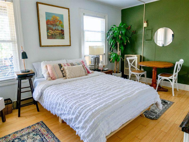 Quarto com decoração estilo boho, móveis de madeira, plantas, abajur azul escuto e paredes verde e branco