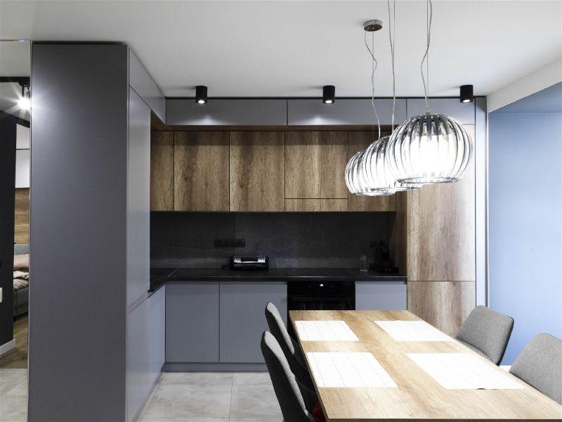 Cozinha moderna e pequena com tons de madeira e cinza, com iluminação sobre mesa de jantar, bem como, por spots espalhados ao redor da cozinha