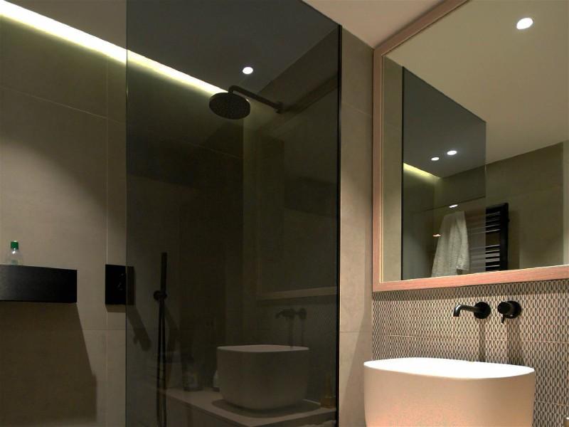 Banheiro com box de vidro escuro, espelho médio na parede, bem iluminado
