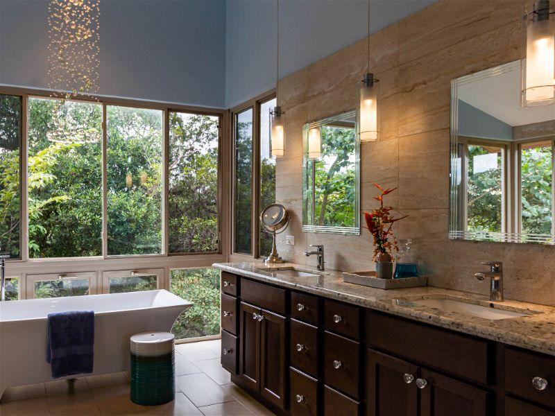 Banheiro no estilo vintage, com iluminação a partir de pendentes e de várias janelas