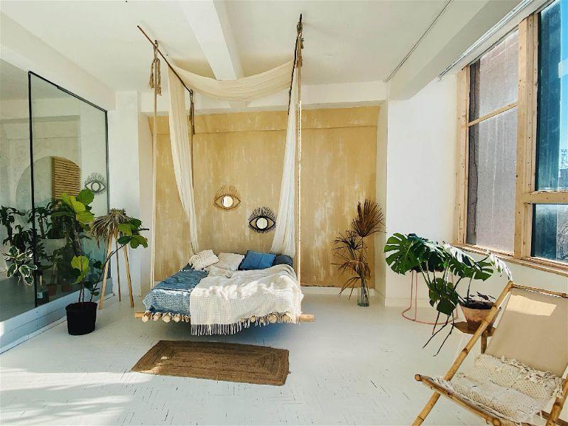Quarto estilo boho, com cama pendura e com tecidos sobrepostos, bem como vasos de planta dispostos no ambiente