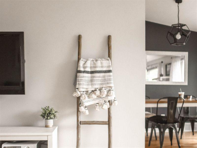 Escada de madeira apoiada em parede com tecido sobre um dos degraus, ao lado de televisão em sala de estar