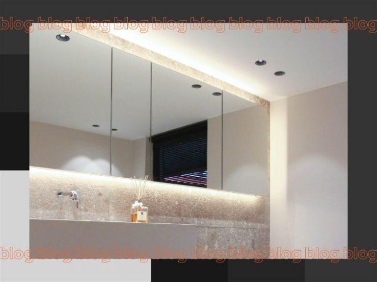 Banheiro com grande espelho e iluminação em volta