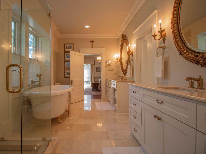 Banheiro grande com decoração branca, iluminação amarelada e arandelas em estilo vintage