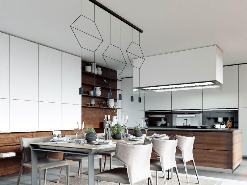 Grande cozinha moderna com móveis planejados, mesa de jantar ao centro com lustres modernos e iluminação sobre bancada da pia