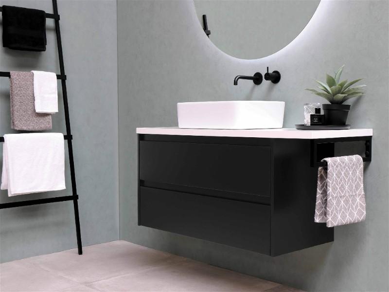 Parte de banheiro moderno com bancada preta e espelho oval na parede com iluminação em volta