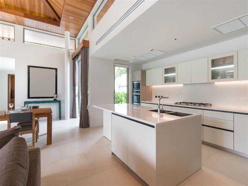 Cozinha moderna com decoração e móveis claros, com iluminação vinda de janela e porta de entrada, bem como, de lâmpadas dispostas em alguns pontos da cozinha