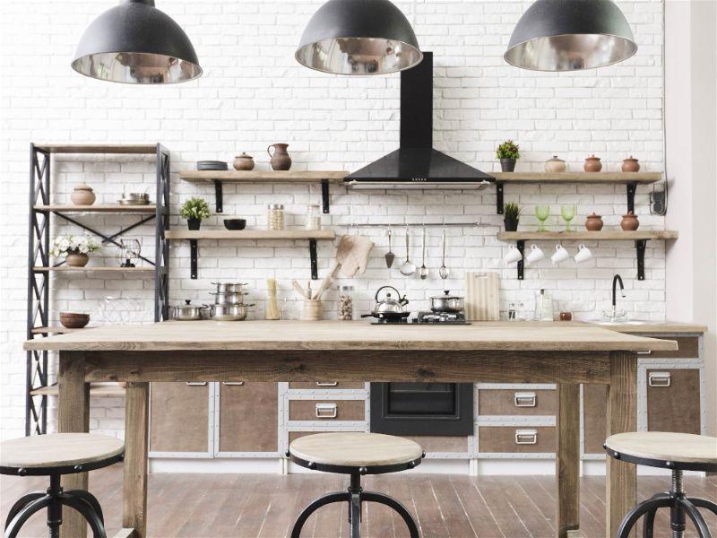 Cozinha no estilo industrial com lâmpadas pendentes sobre mesa ao centro da cozinha
