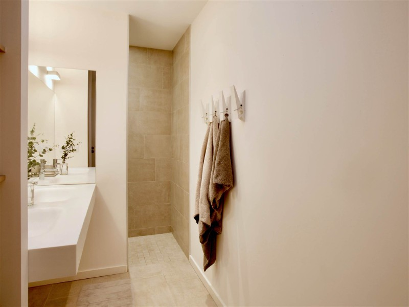 Banheiro com decoração branca e painel de LED refletido em espelho