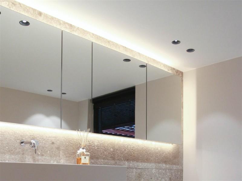 Parede de banheiro toda em espelho com bancada para pia e iluminação com Spot