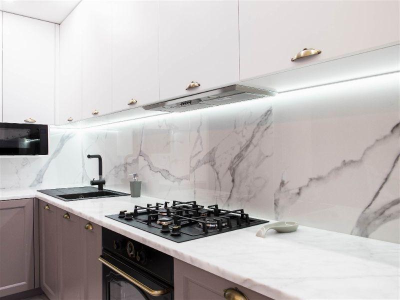 Parte de cozinha com foco em bancada com fogão cooktop e pia, com iluminação forte