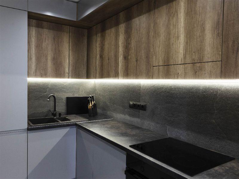 Parte de cozinha com foco em bancada com pia e iluminação baixa