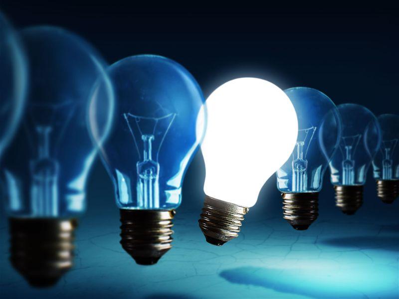 Imagem com tom azulado diversa lâmpadas uma ao lado da outra e apenas uma acesa ao centro