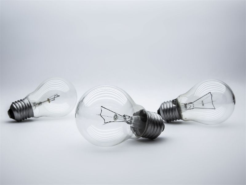Imagem com fundo brando  e três lâmpadas apagadas espalhadas pela imagem