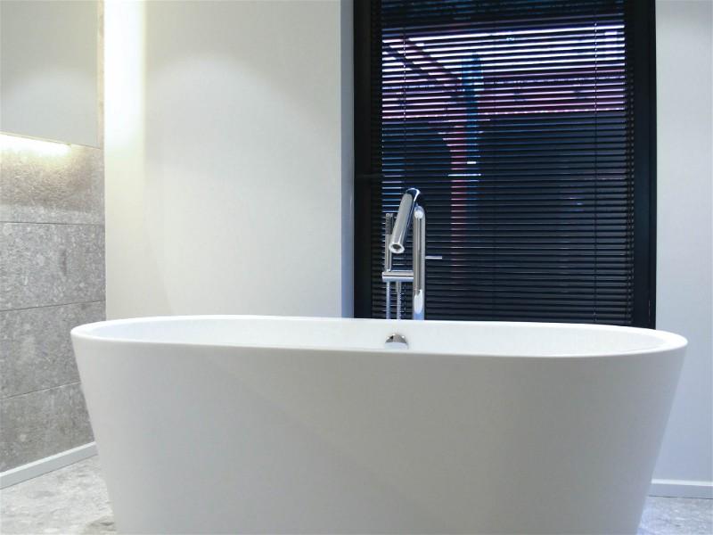 parte de banheiro com banheira moderna e branca, bem iluminada