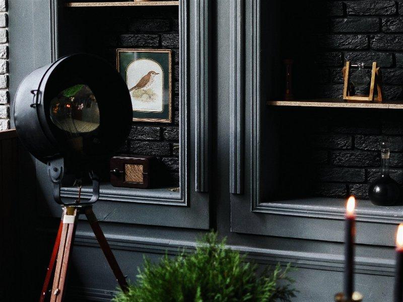 Ambiente com um móvel escuro um abajur apagado  no centro um vaso de planta