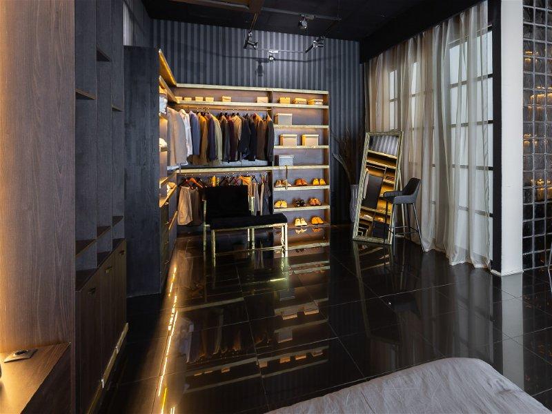Quarto moderno com local para guarda as roupas um pouco escuro, possui uma janela do tamanho da parede coberta com uma cortina leve transparente que permite entrada de luz