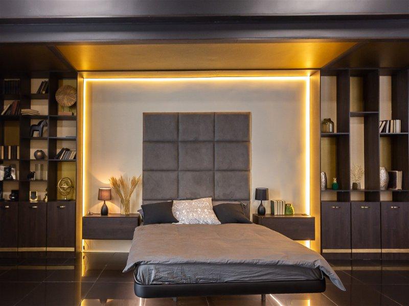 Quarto de casal, onde a cama fica entre móveis que possuem fita de LED ao redor da cabeceira