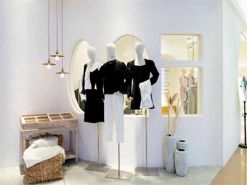 Vitrine de roupas de mulher, manequins com roupas mais formais em cores pretas e brancas.