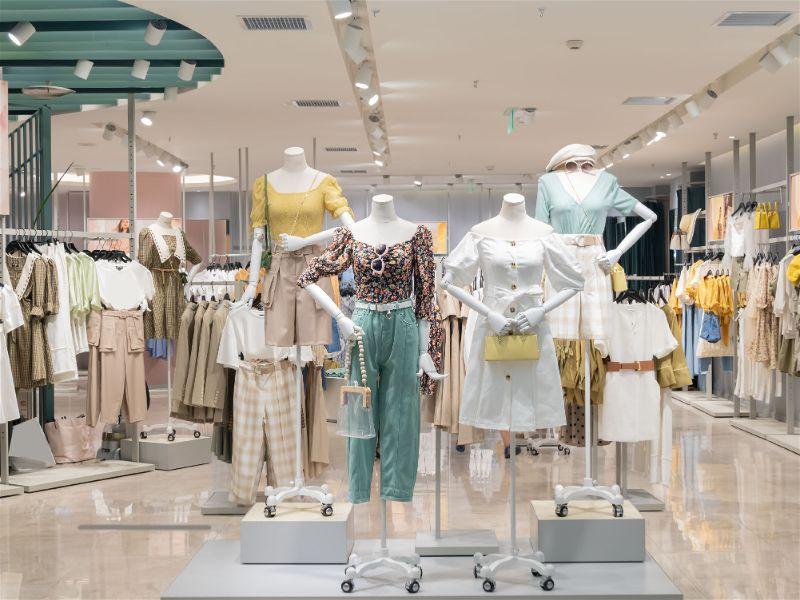 Vitrine de loja de roupas femininas, manequins com roupas e bolsas.