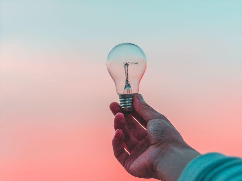 uma mão segurando uma lâmpada incandescente apagada, com o horizonte ao fundo - inventor lâmpada