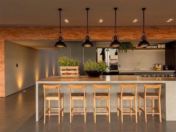área de churrasqueira interna com balcão com cooktop, 5 banquetas, vaso pequeno sobre o balcão, pendentes pretos estilo industrial e pia com torneira ao fundo