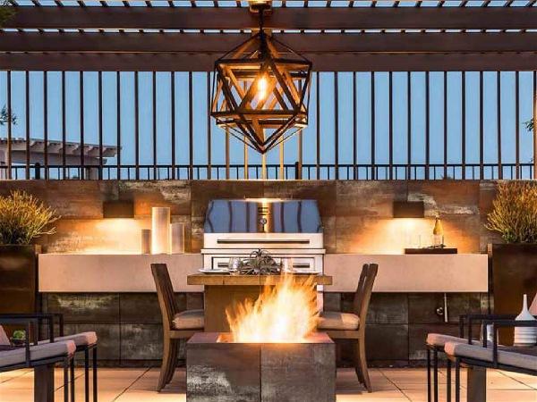 área de churrasco interna com fogueira no centro, mesa, cadeiras, balcão, plantas e algumas grades