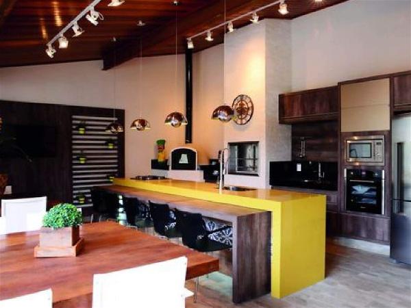 área de churrasco interna com mesa de madeira à esquerda, balcão com banquetas no centro e cozinha integrada