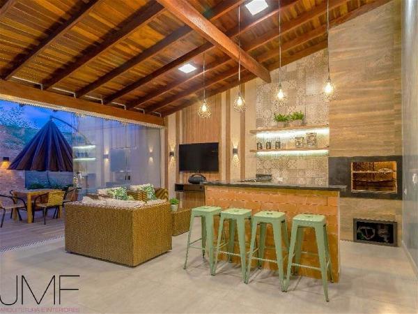 área externa de casa com churrasqueira, forro de madeira, pendentes, 4 banquetas, um sofá de palha e parte descoberta com guarda-sol semi aberto