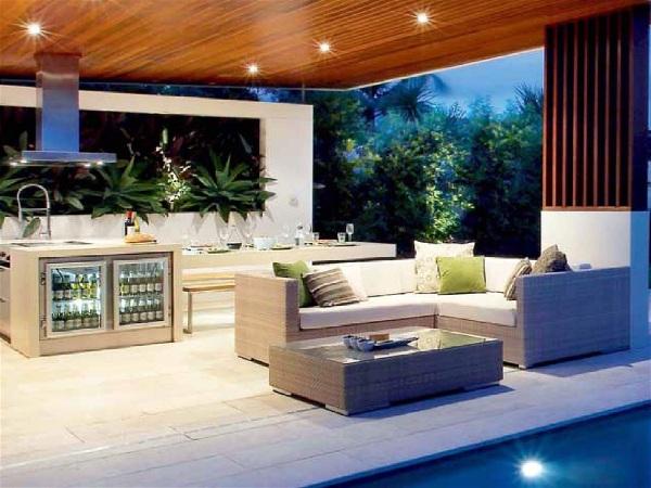 área de churrasco externa coberta ampla, com piso branco, vegetação ao fundo, piscina à frente, mobília em tons neutros, minibar, coifa e spots de luz